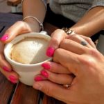 Woman holding coffee and man touching her hand