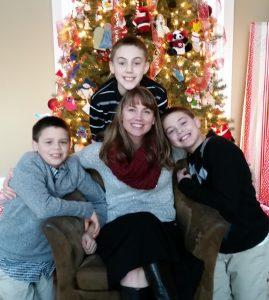 Lorri and boys sitting in front of Christmas Tree