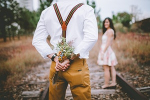 Man holding bouquet behind his back
