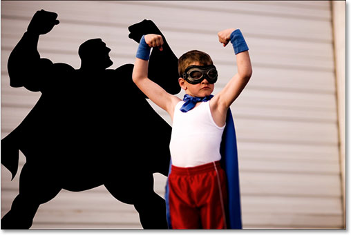 young boy with superhero sized shadow