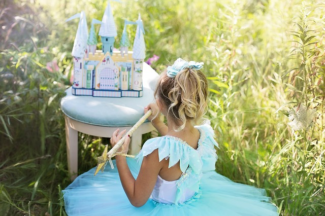 girl dressed as a princess in front of a play castle