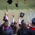 Graduation photo tossing hats by Emily Reinquist