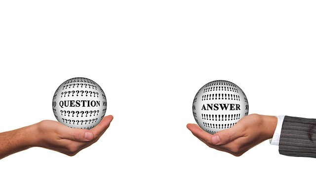 Hands holding question and answer balls