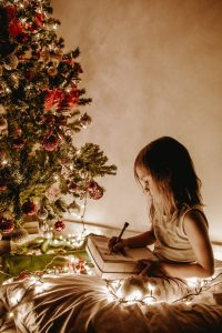 Girl making list under the Christmas Tree