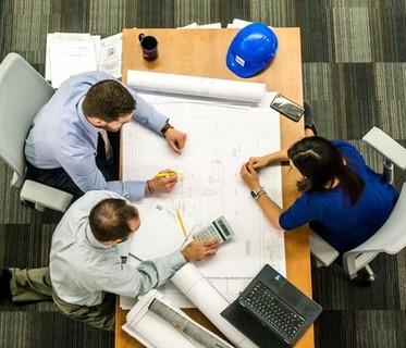Architect, designer, and builder meeting over blueprints
