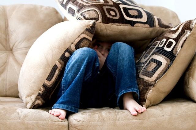 child hiding in couch